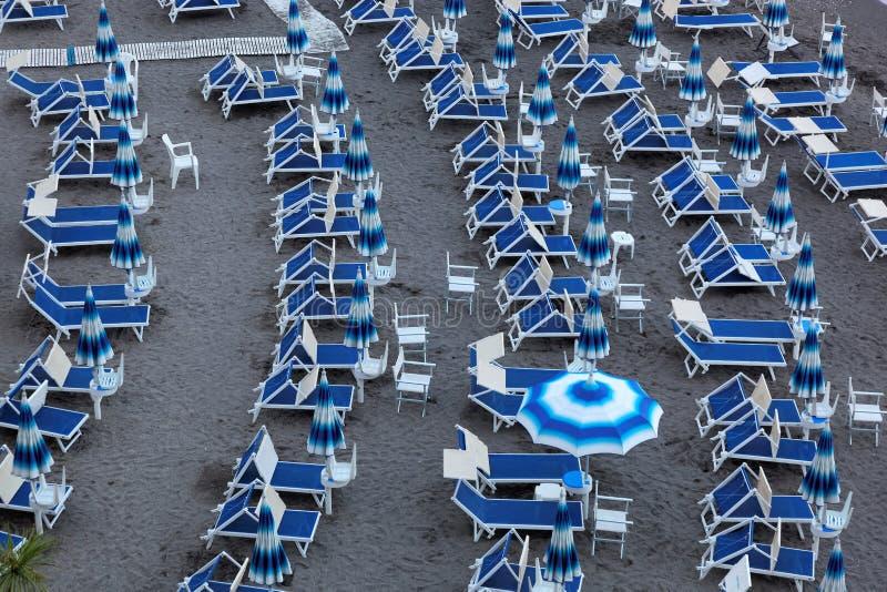Blaue Regenschirme und Liege auf leerem sandigem Strand, Amalfi, Italien lizenzfreies stockbild