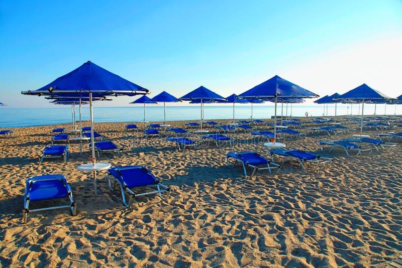 Blaue Regenschirme und Liege auf leerem sandigem Strand, Griechenland stockfotos