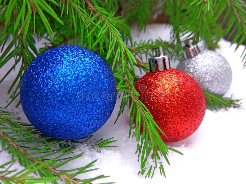 Blaue, rote und silberne Bälle des neuen Jahres mit grünem Tannenbaum auf schneebedecktem Hintergrund lizenzfreies stockfoto