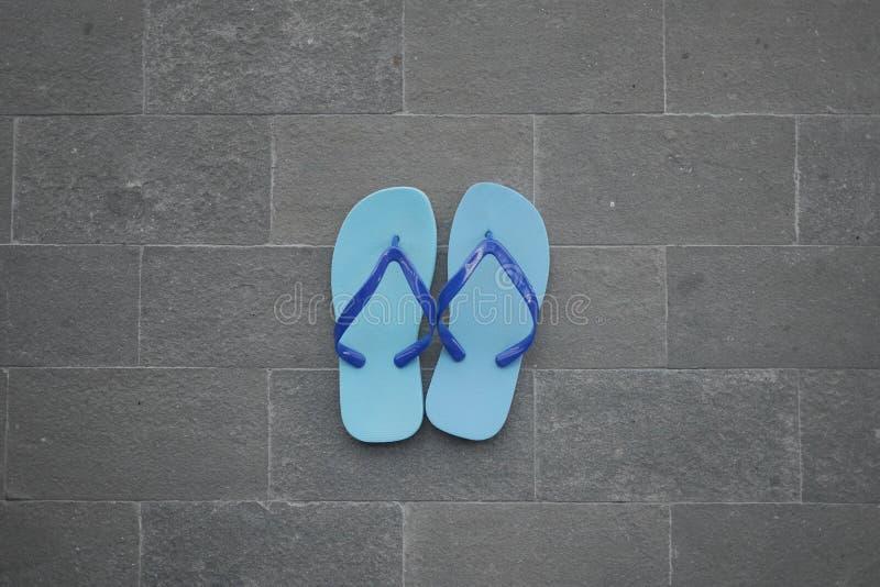 Blaue Sandale auf Ziegelsteinboden lizenzfreies stockfoto
