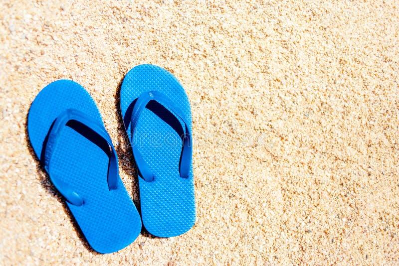 Blaue Sandaleflipflops auf mit gelbem Sand Sommerspaßzeit und ACC lizenzfreie stockbilder