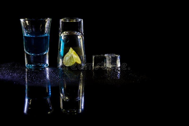 Blaue Schüsse des Cocktails mit Salz und Kalk, Eiswürfel auf schwarzem Hintergrund stockfotos
