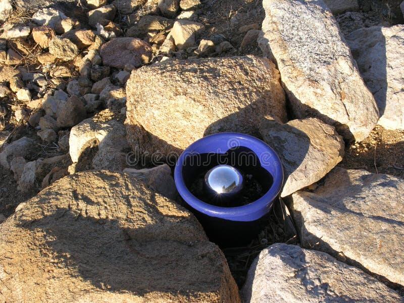 Blaue Schüssel mit Gartenkugel auf Wüstenfelsen stockbilder
