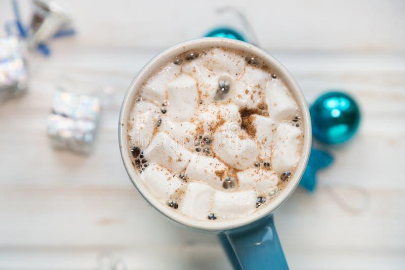 Blaue Schale heißer Kakao mit Eibischen auf weißem hölzernem backgrou stockfotografie