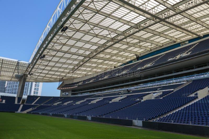 Blaue Sitzplätze, grüne Neigungs-, Galerie-und Glas-Bänke innerhalb des leeren Stadions vor Fußballspiel stockbilder