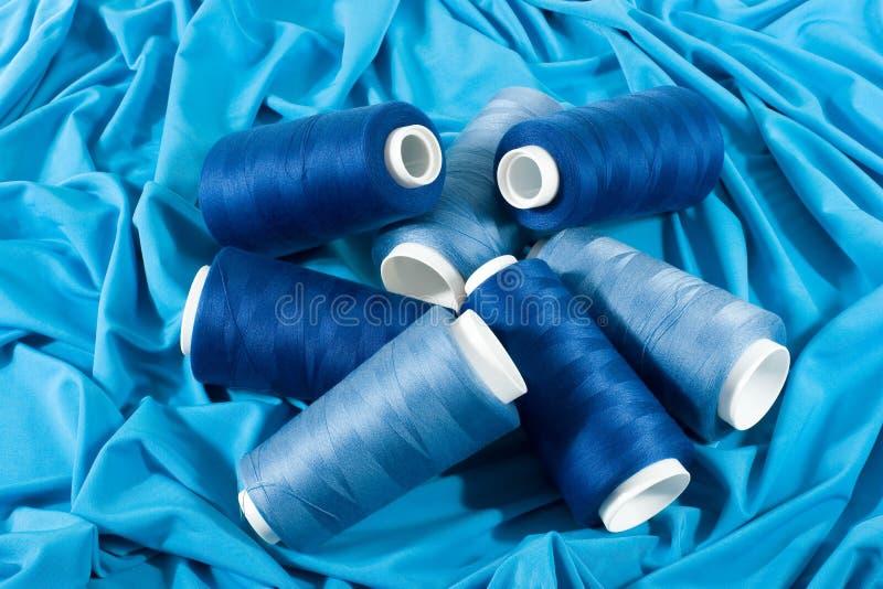 Blaue Spulen der Gewinde auf blauem Tuch stockbilder