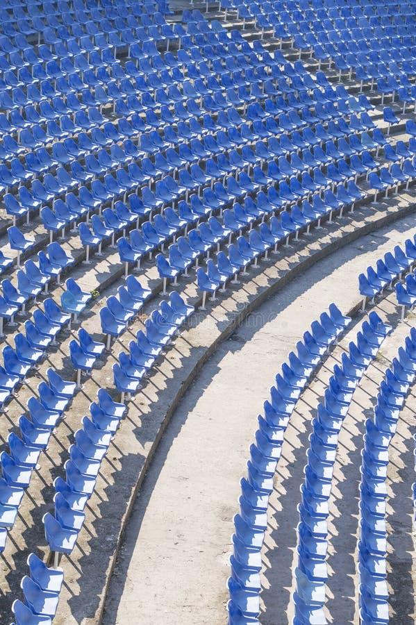 Blaue Stühle in einer leeren Amphitheaterhalle stockfotografie
