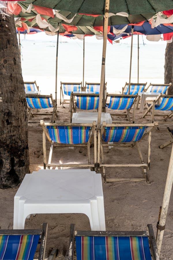 Blaue Strandsegeltuchmietstühle und weiße Tabelle unter buntem u lizenzfreie stockfotos
