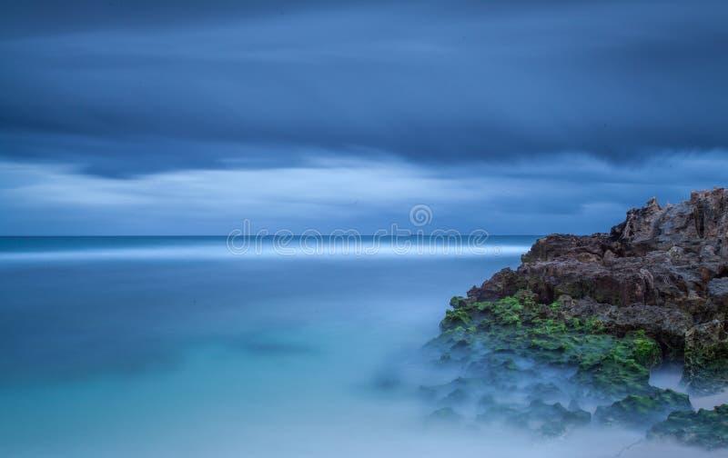 Blaue Strandszene mit Felsen lizenzfreie stockbilder