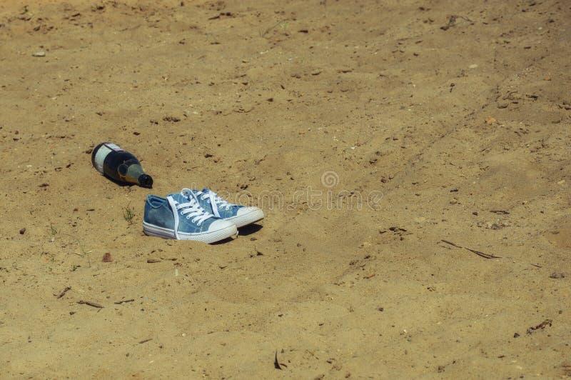 Blaue Turnschuhe des Sports mit Rotzungen und einer Flasche Champagner auf dem Strand stockfotos