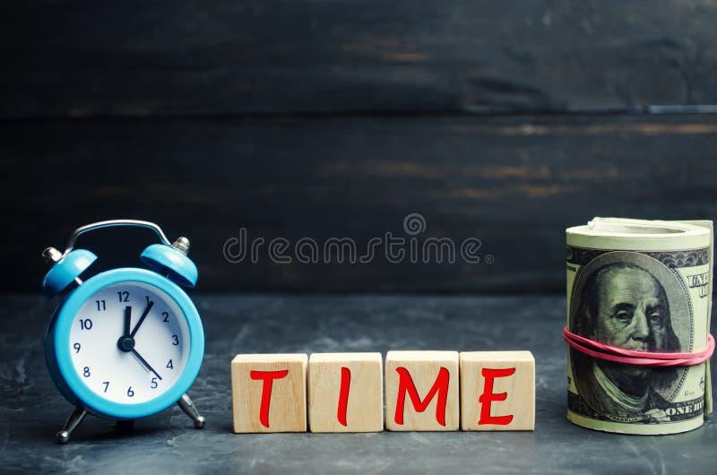 Blaue Uhr, das Aufschrift ` Zeit` und -geld auf einem schwarzen Hintergrund Das Konzept ` zeit- Geldes ` Zeitmanagement Stecken e lizenzfreie stockfotografie