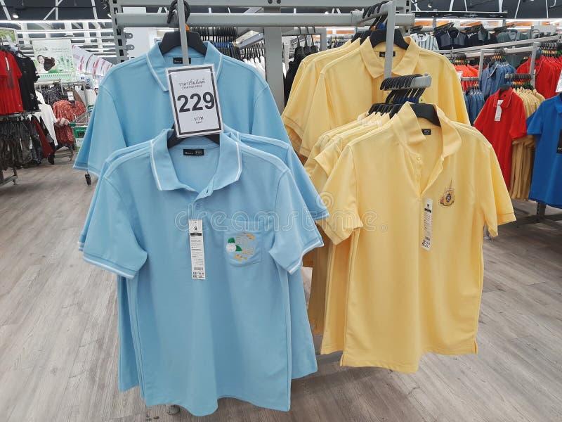 Blaue und gelbe Polohemden, die am Regal für den Verkauf hängen lizenzfreie stockfotos