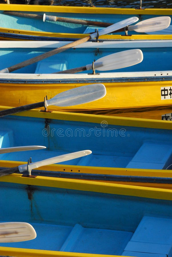 Blaue und gelbe Ruderboote stockbilder