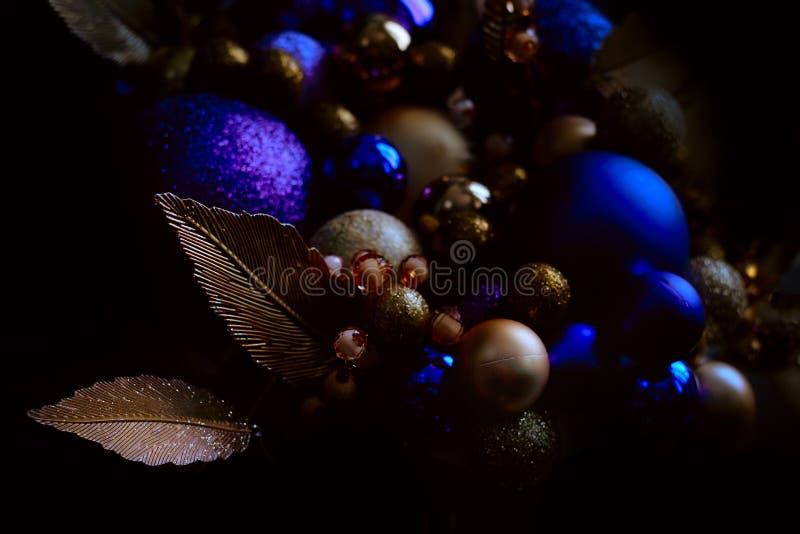 Blaue und goldene Weihnachtsbälle auf einer Weihnachtsbaum-Nahaufnahmeansicht in ein zurückhaltendes mit einem Kopienraum lizenzfreies stockbild