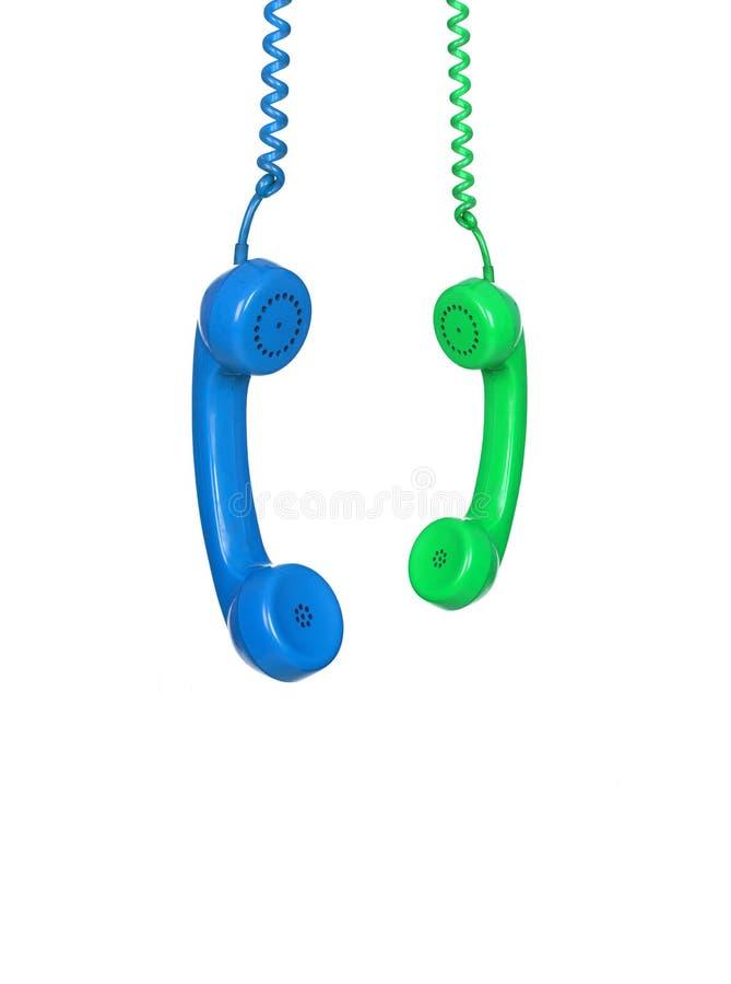Blaue und grüne Telefone, die von einem Kabel hängen stockfotografie