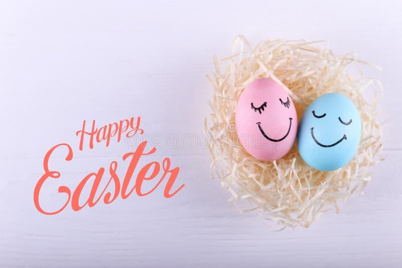 Blaue und rosa Eier mit gemaltem Lächeln im Nest, Kopienraum Glücklicher Ostern-Konzeptgruß-Kartenentwurf lizenzfreie stockbilder
