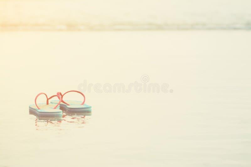 Blaue und rosa Sandale der Paare auf Strand stockfotografie