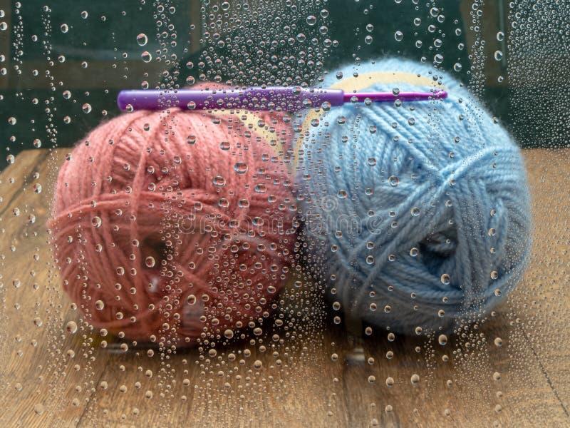 Blaue und rosa Stränge der Wolle mit einer purpurroten Häkelnadel Durch gesehen einem Fenster mit Regentropfen stockbilder
