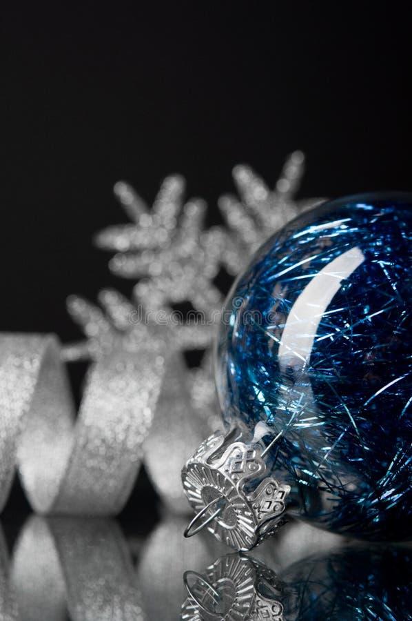 Blaue und silberne Weihnachtsverzierungen auf schwarzem Hintergrund lizenzfreie stockbilder