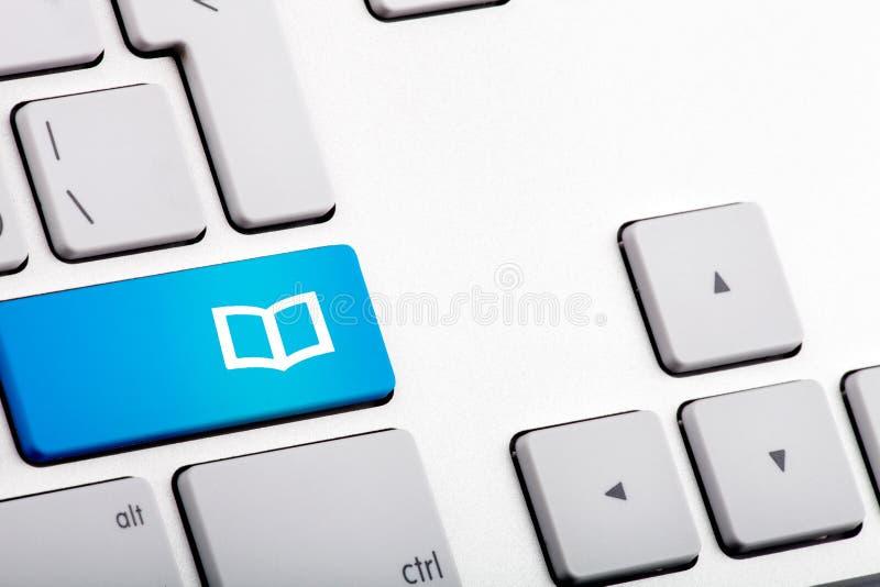 Blaue Unterseite auf einem Laptop mit offenem Buch - nahes hohes lizenzfreies stockbild
