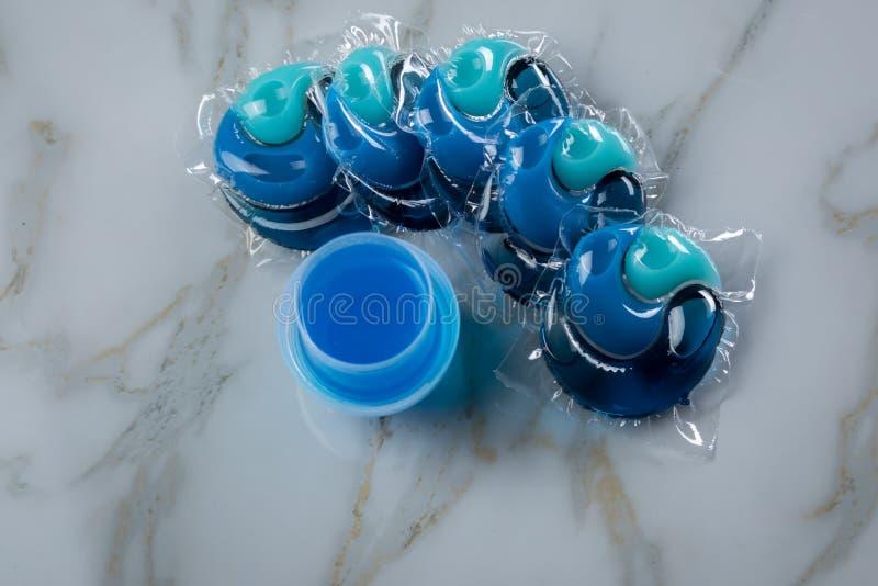 Blaue Waschmittelartvielzahl im flüssigen Gel und in der Hülse in waschender Dosis stockbild