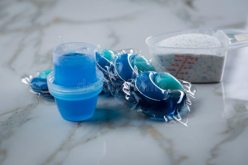 Blaue Waschmittelartvielzahl im Pulver, im flüssigen Gel und in der Hülse in waschender Dosis stockfotografie