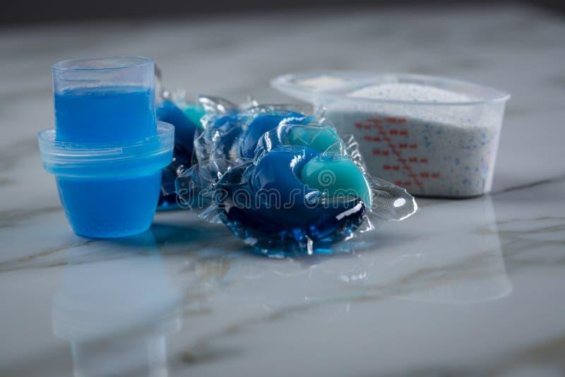 Blaue Waschmittelartvielzahl im Pulver, im flüssigen Gel und in der Hülse in waschender Dosis lizenzfreie stockbilder
