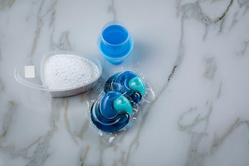 Blaue Waschmittelartvielzahl im Pulver, im fl?ssigen Gel und in der H?lse in waschender Dosis lizenzfreies stockfoto