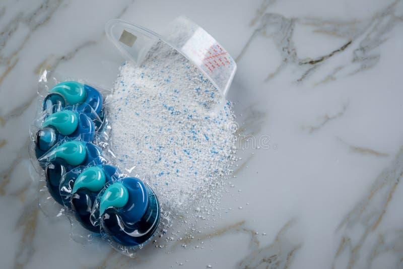 Blaue Waschmittelartvielzahl im Pulver und in der Hülse in waschender Dosis stockfotos