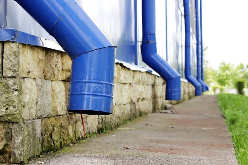 Blaue Wasserleitungen auf großer Sport komplex im Sommer Konzept des Schutzes gegen schwere Regengüsse lizenzfreie stockfotos