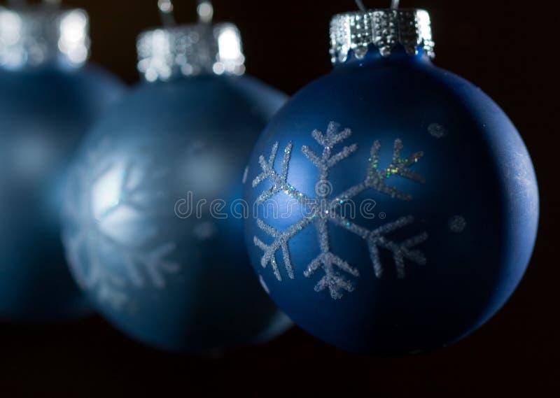Blaue Weihnachtsverzierungen gegen dunklen Hintergrund stockfoto
