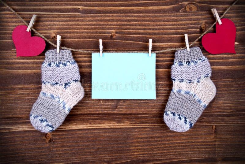 Blauer Aufkleber mit Baby-Socken und Kopien-Raum und Herzen lizenzfreies stockbild