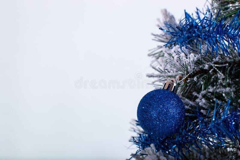 Blauer Ball der Weihnachtsdekoration in einem Baum mit Lametta und pinecone im Schnee stockbild