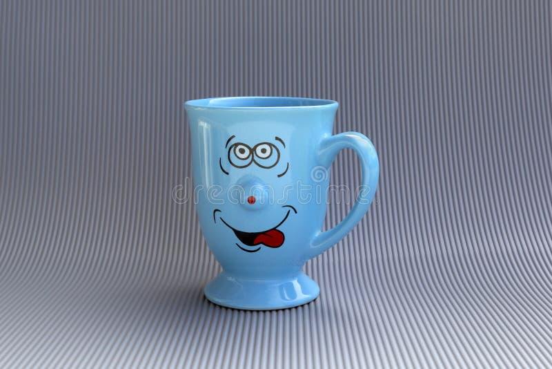 Blauer Becher Kaffee mit glücklichem Lächelngesicht auf grauem Hintergrund Gutenmorgen, kreatives Grußkartenkonzept stockfoto