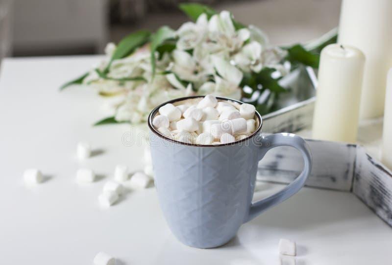 Blauer Becher mit Kakao, Kaffee, Eibische auf weißer Tabelle lizenzfreie stockfotos