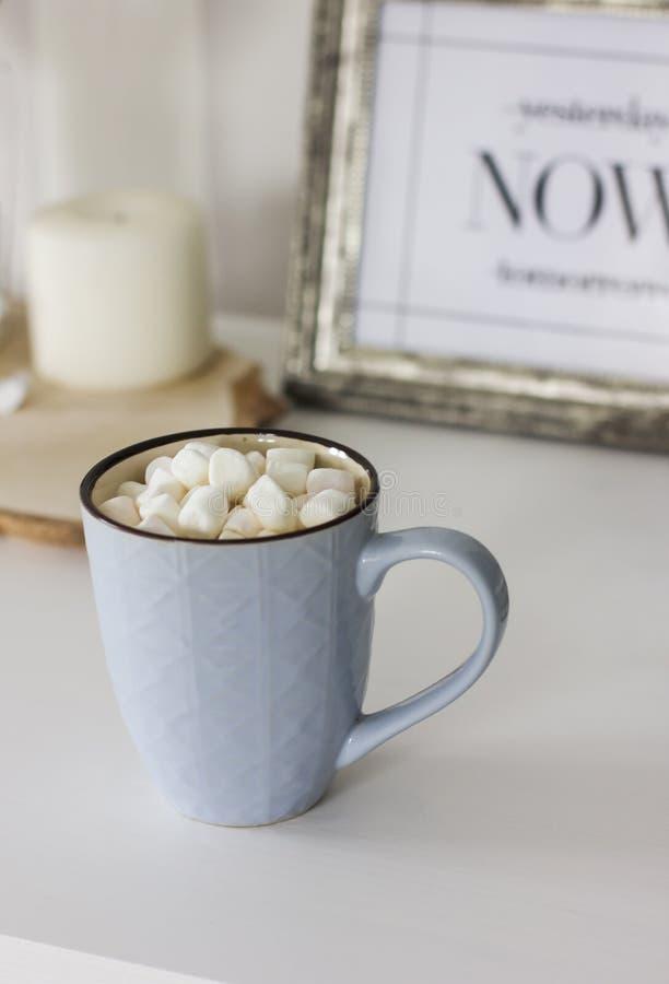 Blauer Becher mit Kakao, Kaffee, Eibische auf weißer Tabelle stockfotografie
