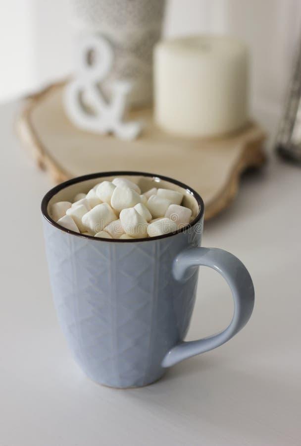 Blauer Becher mit Kakao, Kaffee, Eibische auf weißer Tabelle lizenzfreie stockfotografie