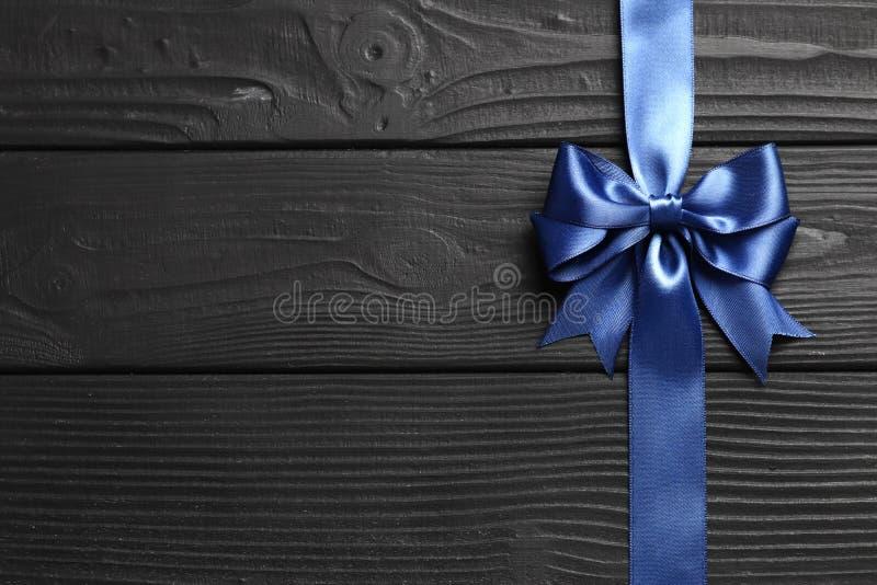 Blauer Bogen und Band des Geschenks auf einem schwarzen hölzernen Hintergrund stockfotos
