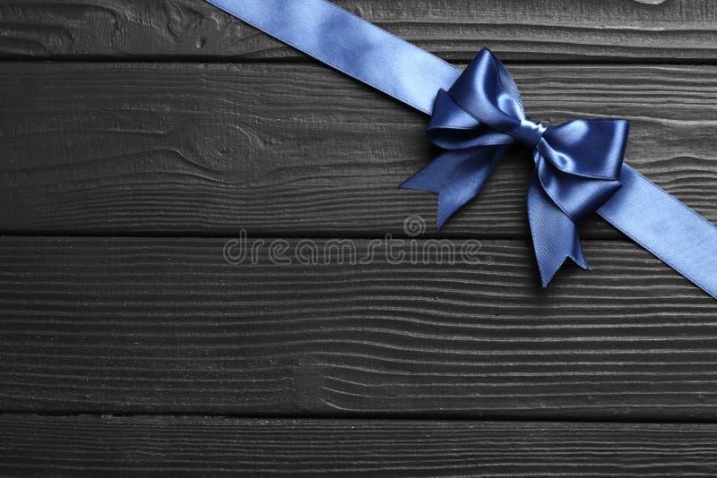 Blauer Bogen und Band des Geschenks auf einem schwarzen hölzernen Hintergrund stockfotografie