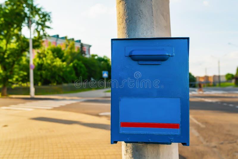 Blauer Briefkasten auf dem grauen Posten stockbilder