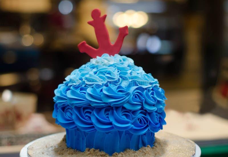 Blauer buttercream Kuchen mit rotem Anker vor Kuchenspeicher lizenzfreie stockfotografie