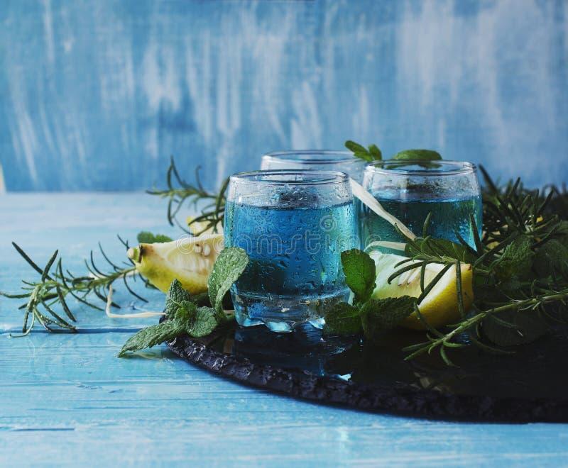 Blauer Curaçao-Likör oder -sambuca mit Zitrone lizenzfreie stockfotos