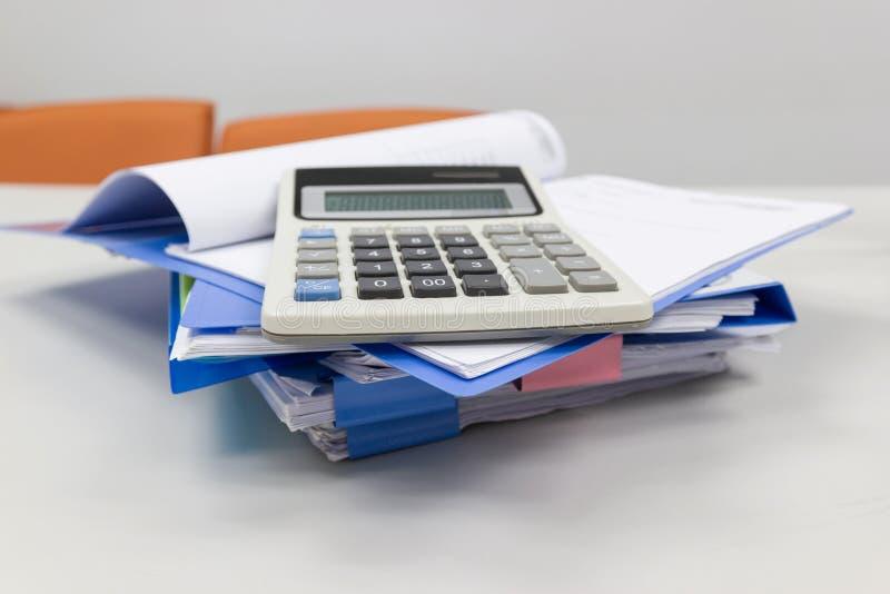 Blauer Dateiordner mit Papier, Berechnung auf dem Tisch im Arbeitsbüroraum lizenzfreies stockbild