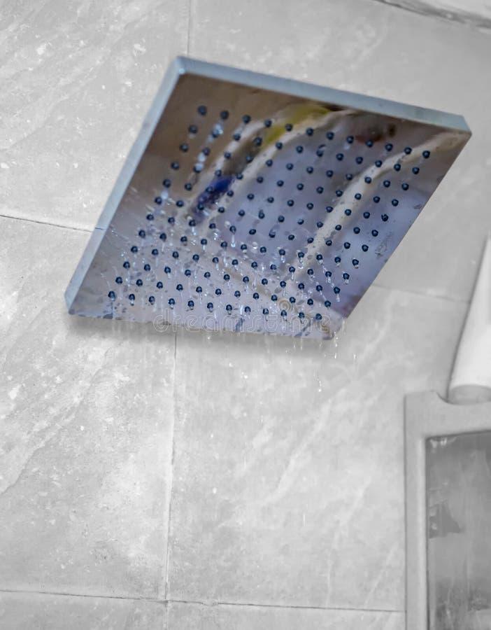 Blauer Duschkopf mit flüssigen Wassertropfen stockfoto
