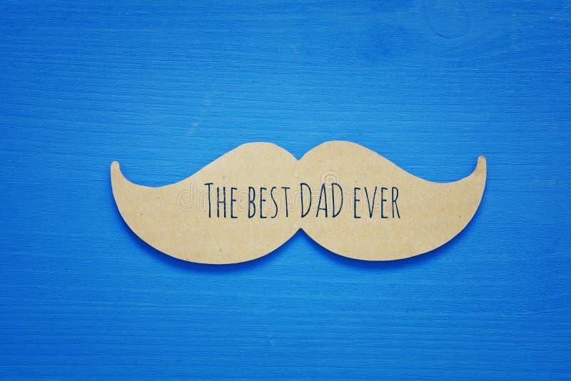 Blauer hölzerner Hintergrund und Papierschnurrbart Vatertagskonzept lizenzfreie stockbilder