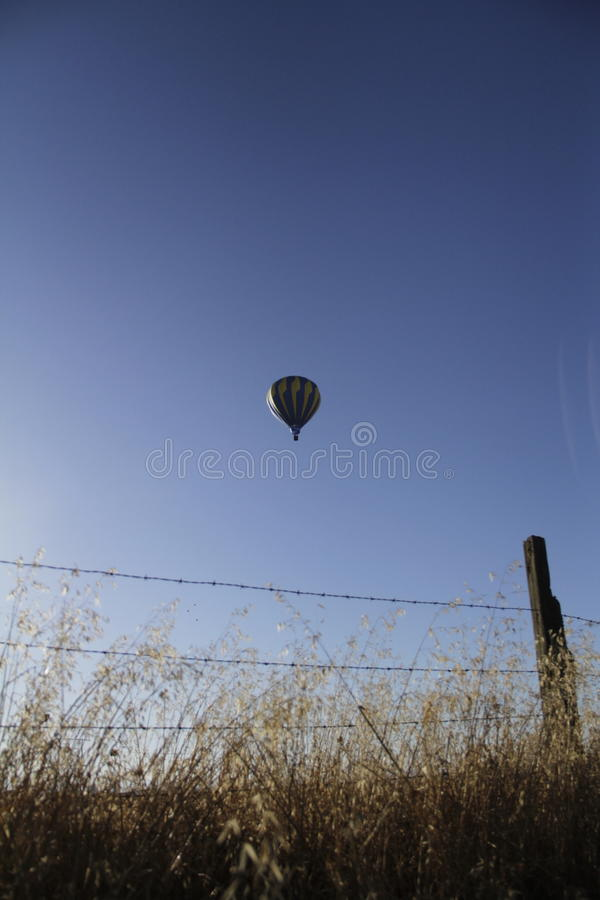 Blauer Heißluft-Ballon über Zaun lizenzfreies stockbild