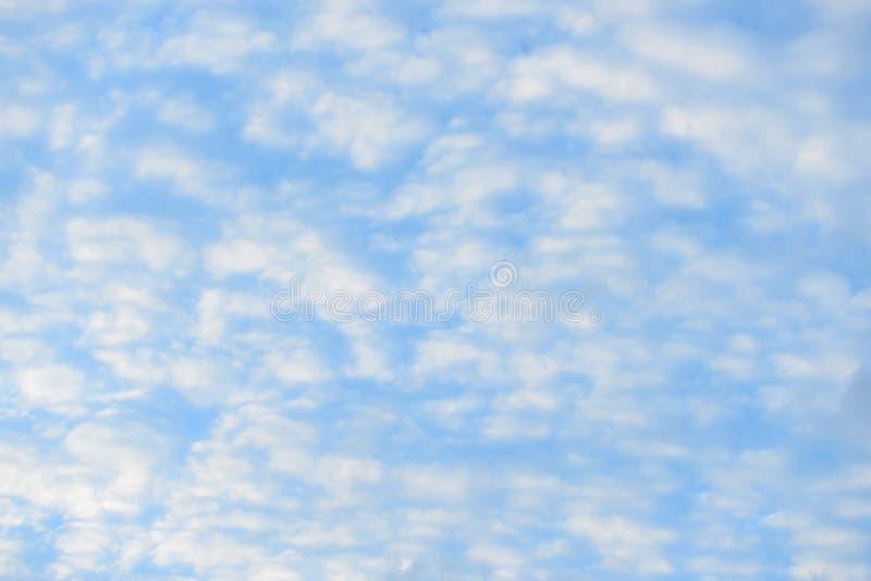 Blauer Himmel mit flaumigen Wolken, Nahaufnahmehintergrund stockfotografie