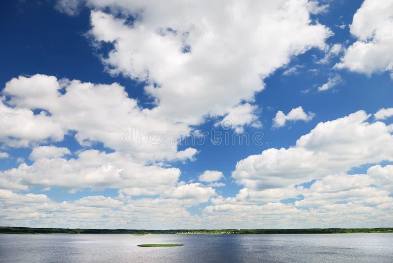 Blauer Himmel mit Wolken über See stockbilder
