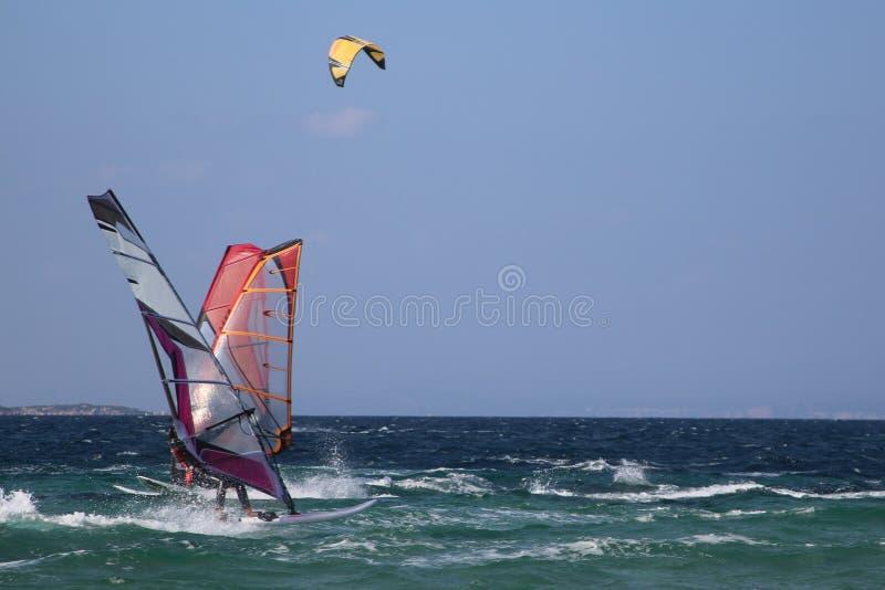 Blauer Himmel und bewegter See mit Windsurfers und kitesurfer Porto Pollo, Sardinien, Italien lizenzfreies stockfoto