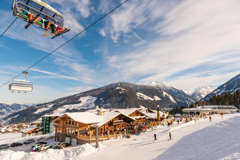 Blauer Himmel und liftchait über Gebirgsrestaurant und schneebedecktes Dach und Berge am Hintergrund lizenzfreie stockfotos